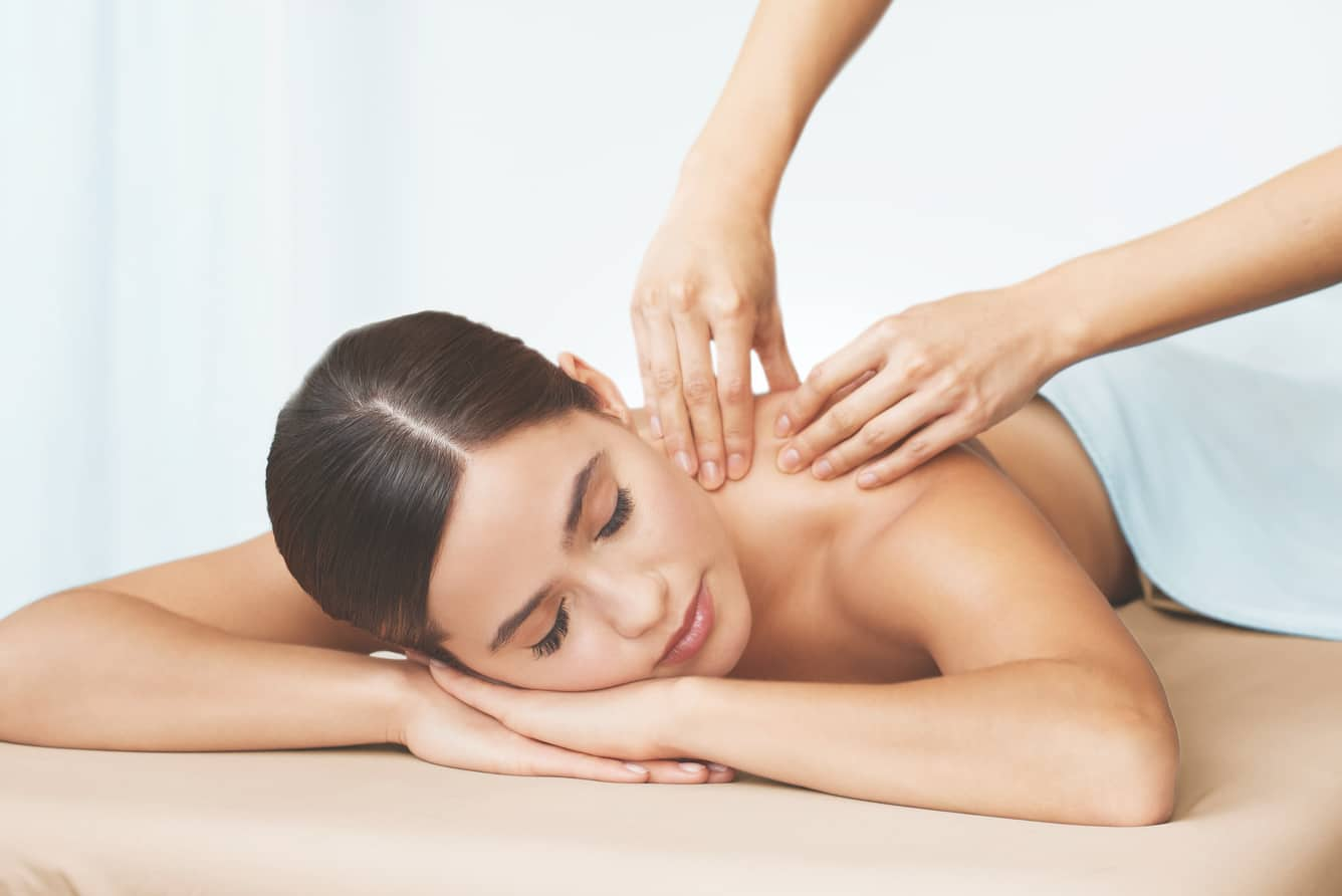two hands massaging a woman's shoulder at the Life Time Spa