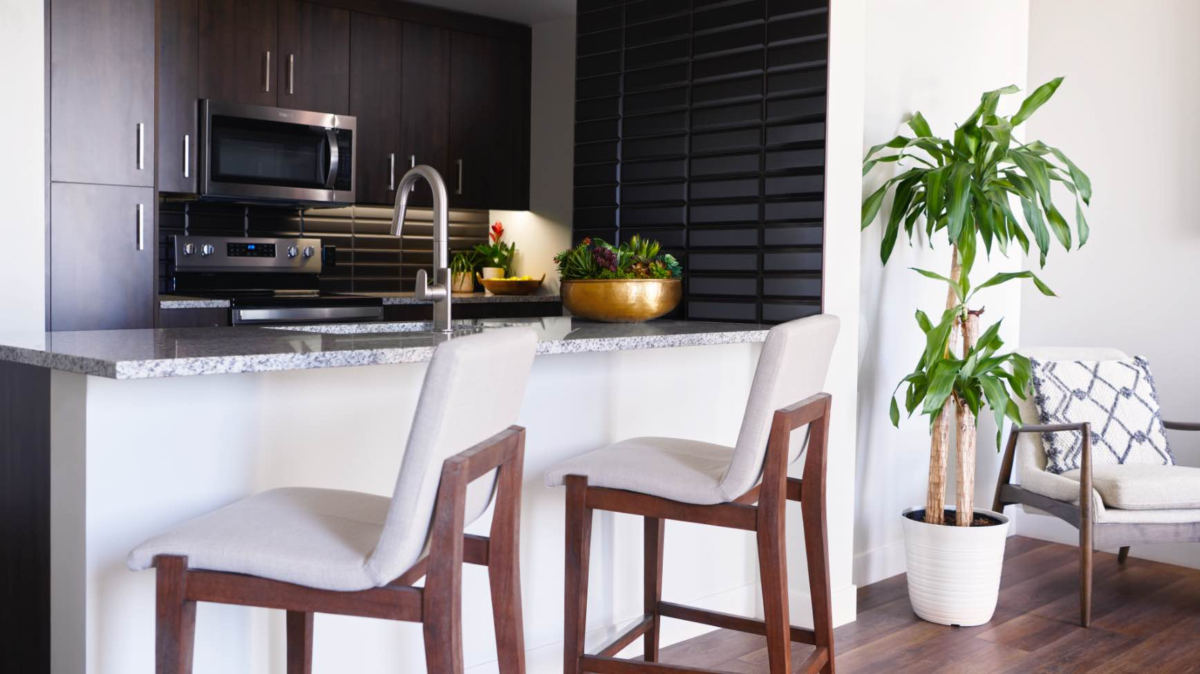 two white bar stools looking into a kitchen