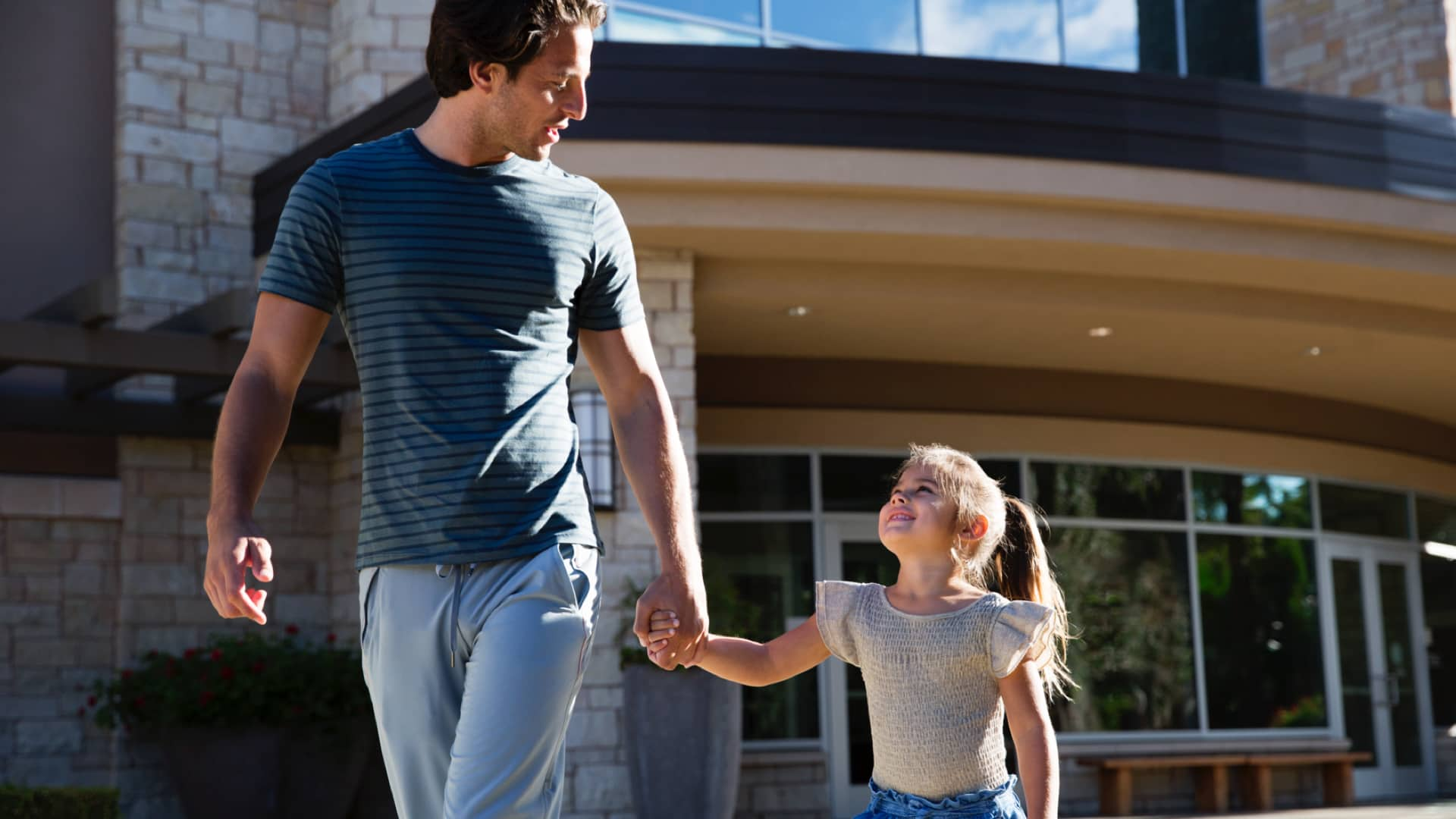 A father and daughter walk together in front of a Life Time Athletic Resort and Spa
