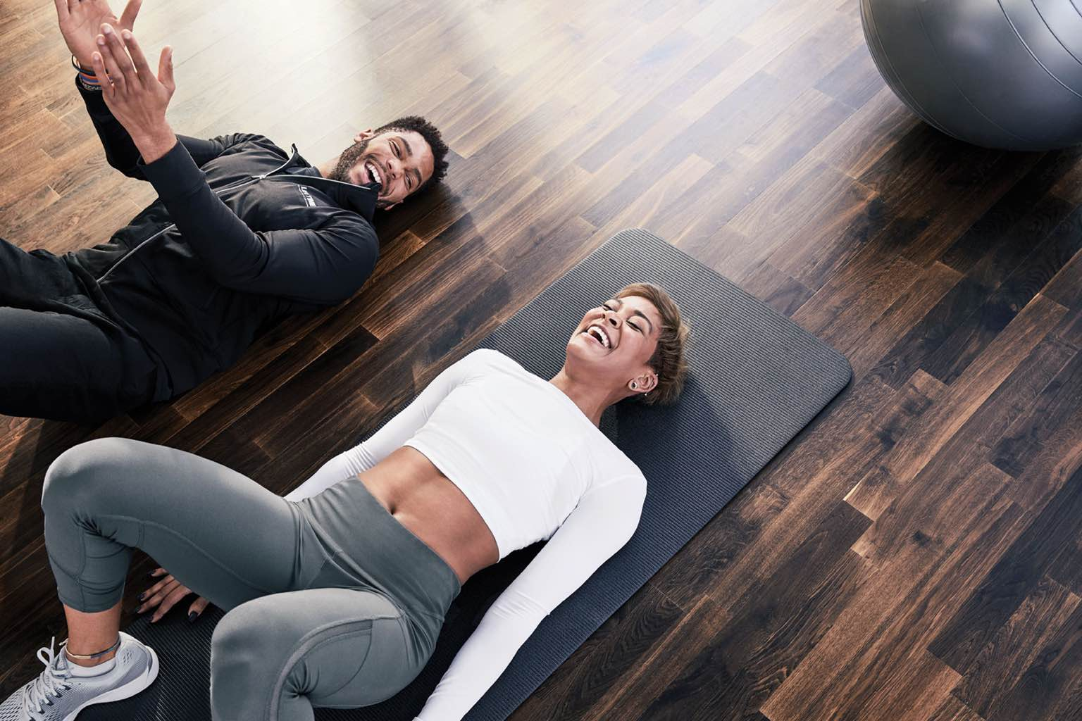 Two people lying on yoga mats laughing in a group fitness studio