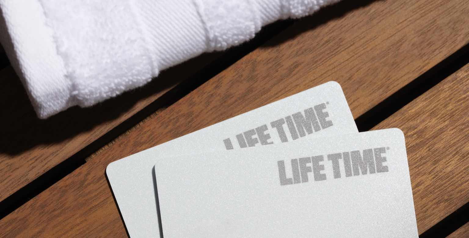A photo of two Life Time membership cards on a wooden bench.